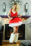 Die junge schöne blonde Frau, die als sexy Sankt-Helfer in der roten Kleider- und Fischnetzstrumpfware aufwirft im Weihnachten ge Stockbild