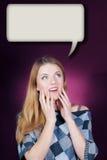 Junge Frau, die oben in der Verwunderung auf Dialogfeld schaut Lizenzfreie Stockfotografie