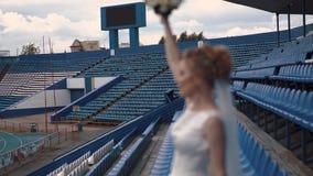 Die junge schöne Braut, defocused, steht im Stadion stock video footage