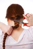 Die junge schöne Frau schneidet rotes langes Haar lizenzfreie stockbilder