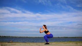 Die junge schöne sexy Frau, die Sport auf Strand, Sonnenaufgang tut, Morgen trainiert und hört Musik auf den Kopfhörern, gesund stock video