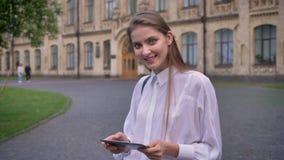 Die junge schöne Studentin arbeitet an ihrer Tablette im Sommer und lächelt und passt an der Kamera, Kommunikationskonzept auf stock video footage