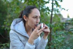 Die junge Schönheit, die heißen Tee von einer Thermosflasche trinkt, höhlen draußen Stockfoto