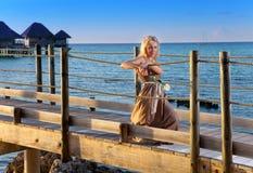 Die junge Schönheit in einem langen dress.portrait gegen das tropische Meer stockfotografie