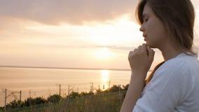 Die junge Schönheit, die an Gott in der Natur, das betende Mädchen sich wendet, faltete ihre Hände am Kinn, Konzept der Religion stock video footage