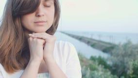 Die junge Schönheit, die an Gott in der Natur, das betende Mädchen sich wendet, faltete ihre Hände am Kinn, Konzept der Religion stock video