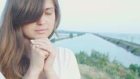 Die junge Schönheit, die an Gott in der Natur, das betende Mädchen sich wendet, faltete ihre Hände am Kinn, Konzept der Religion stock footage