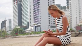 Die junge Schönheit, die mit dem langen blonden Haar im Schwarzweiss-Kleid dünn ist, sitzt auf dem Strand und benutzt einen Smart stock video footage