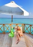Die junge schlanke Frau das blonde Ein Sonnenbad nehmen liegt auf einem Wagenaufenthaltsraum gegen den tropischen Ozean Stockbilder