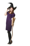 Die junge schöne Hexe mit einem Besen und einem Hut Lizenzfreies Stockfoto