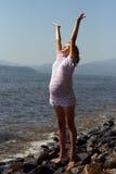 Die junge schwangere Frau und das Meer Stockbild