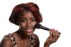 Die junge schwarze Frau, die sich an setzt, erröten Make-up Stockfoto