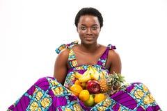 Die junge sitzende und haltene Frau des netten schönen Afroamerikaners trägt Früchte Stockfotografie
