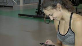 Die junge Sportlerin sitzt in der Turnhalle und liest das messege auf ihrem Smartphone stock footage