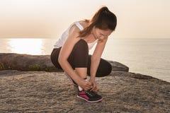 Die junge sportliche Frau, die sich vorbereitet, in Morgen und Meer zu laufen, ist backgr Stockbilder