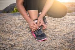 Die junge sportliche Frau, die sich vorbereitet, in Morgen und Meer zu laufen, ist backgr Stockfotos