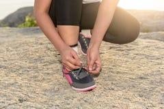 Die junge sportliche Frau, die sich vorbereitet, in Morgen und Meer zu laufen, ist backgr Lizenzfreie Stockfotos