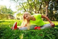 Die junge sportliche Frau, die Eignung tut, übt das Ausdehnen in Park aus Lizenzfreie Stockbilder