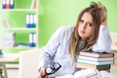 Die junge Studentin, die für Prüfungen mit vielen Büchern sich vorbereitet stockbild