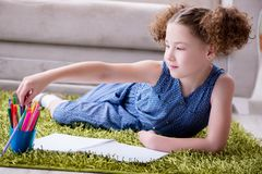 Die junge Zeichnung des kleinen Mädchens auf Papier mit Bleistiften stockbild