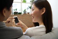 Die jungen asiatischen Paare, die auf Sofa sitzen, betrachten das Mobiltelefon lizenzfreie stockfotos