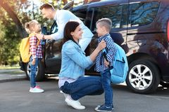 Die jungen Eltern, die von ihren Kindern Abschied nehmen, nähern sich Schule stockfotos