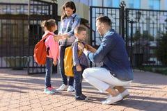 Die jungen Eltern, die von ihren Kindern Abschied nehmen, nähern sich Schule stockfotografie