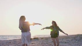 Die jungen Frauen der Zeitlupe, die in boho Art gekleidet werden, haben Spaß auf der Küste am Abend in den Strahlen des Sonnenunt stock video