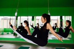 Die jungen Frauen, die Antigravitationsyoga machen, trainiert mit einer Gruppe von Personen aero Fliegeneignungs-Trainertraining  Stockfoto