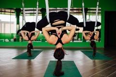 Die jungen Frauen, die Antigravitationsyoga machen, trainiert mit einer Gruppe von Personen aero Fliegeneignungs-Trainertraining  Lizenzfreies Stockfoto