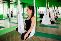 Die jungen Frauen, die Antigravitationsyoga machen, trainiert mit einer Gruppe von Personen aero Fliegeneignungs-Trainertraining  Stockfotos