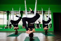 Die jungen Frauen, die Antigravitationsyoga machen, trainiert mit einer Gruppe von Personen aero Fliegeneignungs-Trainertraining  Lizenzfreies Stockbild
