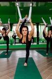 Die jungen Frauen, die Antigravitationsyoga machen, trainiert mit einer Gruppe von Personen aero Fliegeneignungs-Trainertraining  Stockbilder