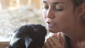 Die jungen Frauen, die Schafe und Ziege einziehen, essen ihr Haar stock video footage