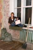Die jungen Frauen sitzt an einem Fenster in schmutzigem Stockfotografie