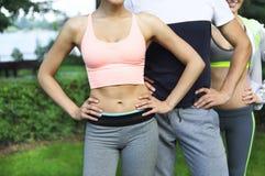 Die jungen Freunde, die Muskeln vor Sport ausüben und ausdehnen, fungieren Stockfoto