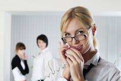 Die junge Geschäftsfrau im Büro mit Kollegen Lizenzfreies Stockbild