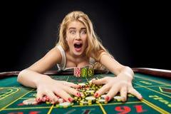 Die jungen hübschen Frauen, die Roulette spielen, gewinnt am Kasino stockfotos