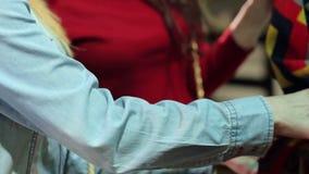 Die jungen Mädchen, die Kleidung in einem Speicher wählen, sortieren sie heraus Kleidung auf Aufhänger stock video footage