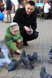 Die Jungen mit Mutter auf den quadratischen Zufuhrtauben lizenzfreie stockfotos