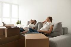 Die jungen Paare, die auf Couch bewegten sich entspannen gerade sich, in neues Haus stockbilder