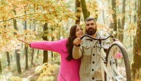 Die jungen Paare, die das Fahrrad und den Betrieb weg von der Büroarbeit nehmen Tragende gestrickte Strickjacken Zusammen gehen lizenzfreies stockbild