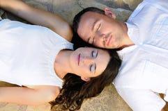 Die jungen Paare, die auf einem Steinboden mit Augen liegen, schlossen Lizenzfreie Stockfotografie