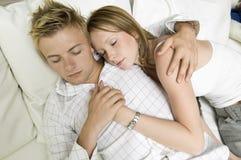 Die jungen Paare, die auf Sofa schließen liegen zusammen, herauf hohe Winkelsicht Lizenzfreies Stockbild