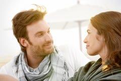 Die jungen Paare, die auf Sommer sitzen, setzen das Lächeln auf den Strand Lizenzfreie Stockfotos