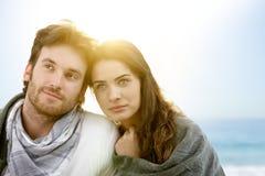Die jungen Paare, die auf Sommer sitzen, setzen mit Decke auf den Strand Lizenzfreie Stockfotografie