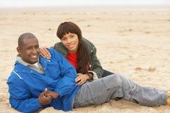 Die jungen Paare, die auf Winter sich entspannen, setzen Feiertag auf den Strand Lizenzfreies Stockfoto