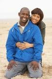 Die jungen Paare, die auf Winter sich entspannen, setzen Feiertag auf den Strand Stockbild