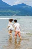 Die jungen Paare, die durch das Wasser im Porzellan laufen, setzen Danang auf den Strand Lizenzfreie Stockfotografie