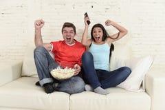 Die jungen Paare, die fernsehen, tragen das Fußballspiel aufgeregte Feiern zur Schau Lizenzfreie Stockbilder